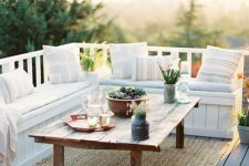 a small deck with a built-in seating with printed pillows, a low table, a jute rug and potted plants is a chic and cool space