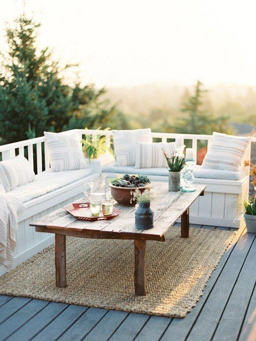 a small deck with a built in seating with printed pillows, a low table, a jute rug and potted plants is a chic and cool space
