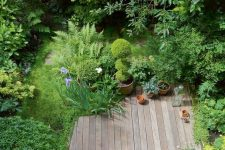 a small deck with a folding chair, potted plants and blooms is a lovely space to relax for just one person