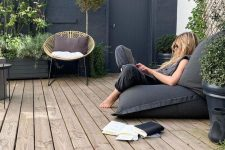 a small deck with a rattann and a beanbag chair, potted plants and mini trees is a very welcoming and fresh space