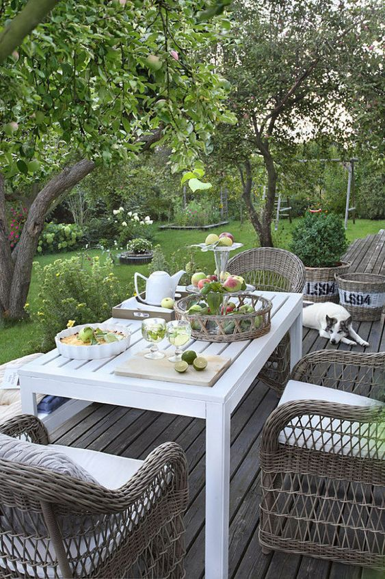 a small deck with a white table and woven chairs is a pretty and cool space to dine outdoors is amazing