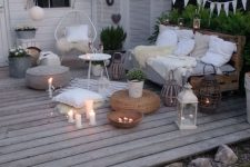 a small deck with an outdoor Scandinavian living room, pallet and rattan furniture, poufs and candles plus string lights