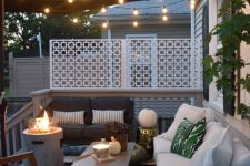 a small deck with an umbrella and string lights, modern white and black furniture, a coffee table and a fire pit plus greenery