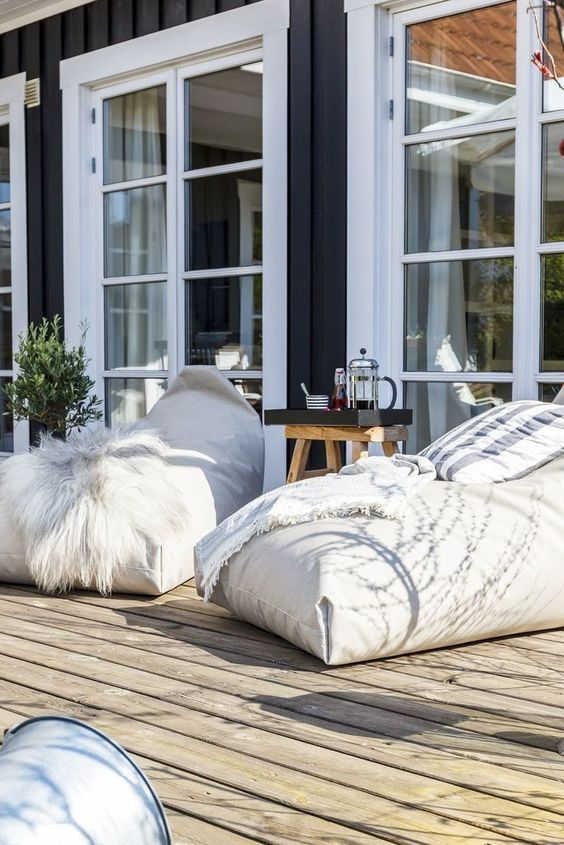 a small deck with beanbag chairs, a mini side table and a tray, a potted plant is a very cozy and cute space