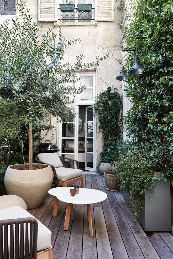 a small deck with lots of potted trees and plants all around, a couple of chairs and a small coffee table is a cool and welcoming outdoor nook