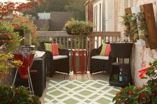 a small deck with potted blooms and plants, woven dark furniture, a bold rug and a mini pond plus a mini bar