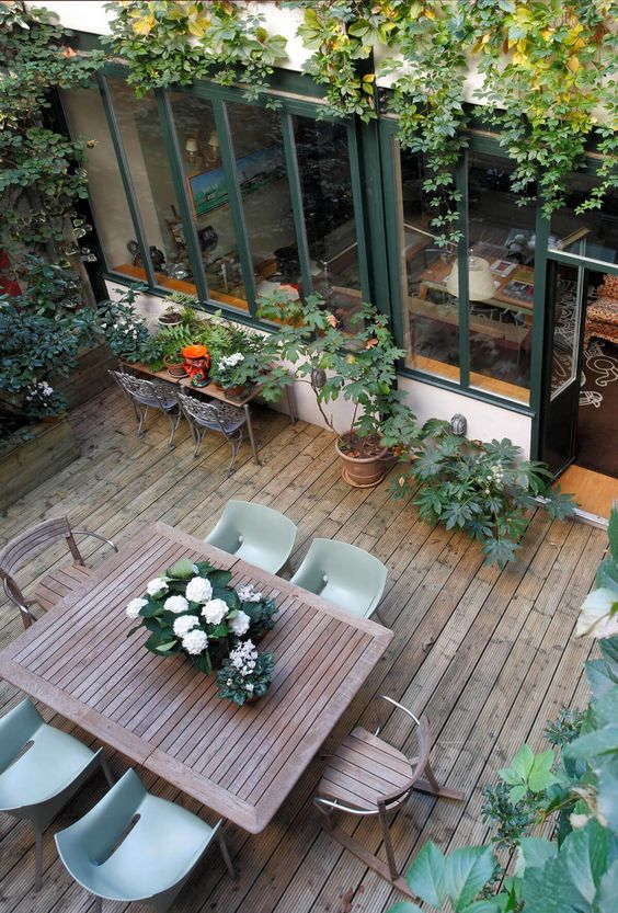 a small deck with potted plants and vines covering the space, a wooden table and chairs, a small gardening table is welcoming