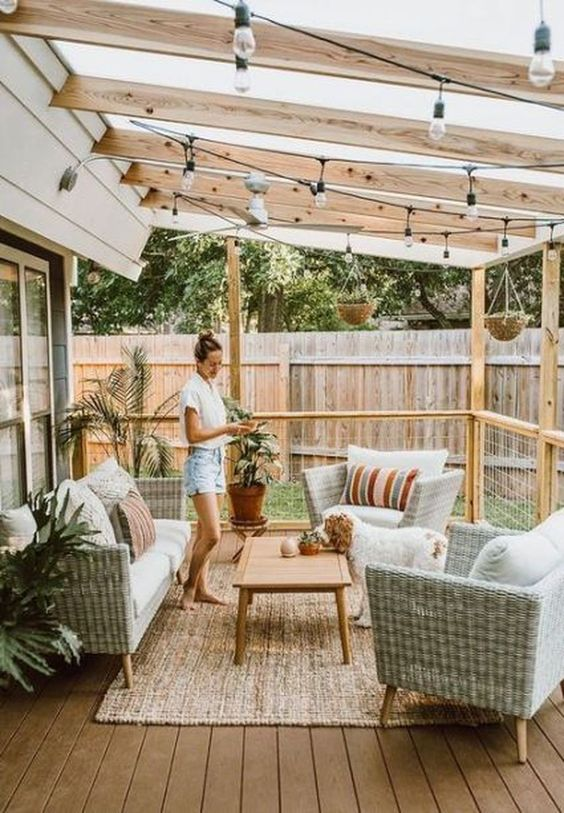 a small deck with woven furniture, a low coffee table, potted plants and string lights over the space is a chic idea
