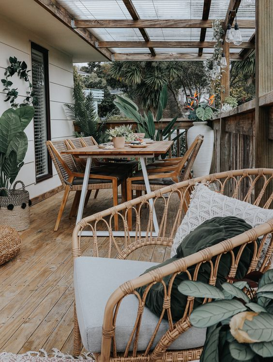 a small desk with a dining space with rattan chairs plus a rattan chaur with pillows and potted plants is a chic space