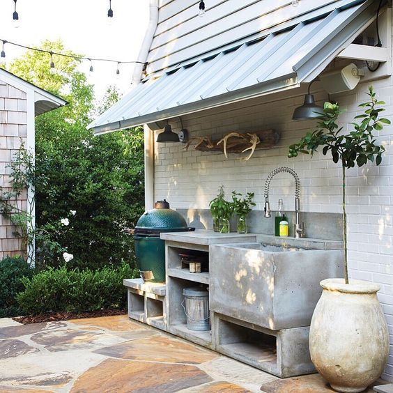 a small minimalist concrete kitchen with open storage compartments, a grill and a large sink plus potted herbs is very cool and practical