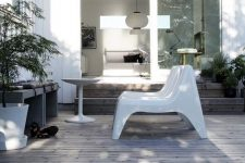 a small minimalist deck with a bench with cushions, white loungers, a coffee table, potted plants is a chic and cool space