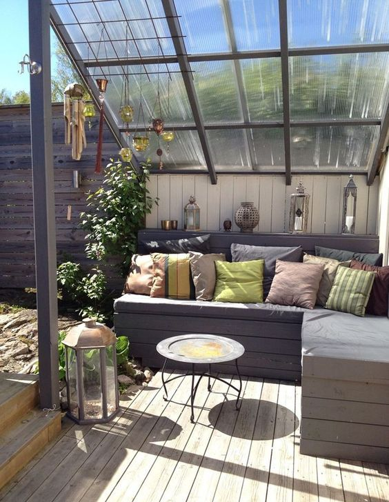 a small modern rooftop terrace with a wooden deck, a wooden bench, colorful pillows and a large framed grass roof over the nook