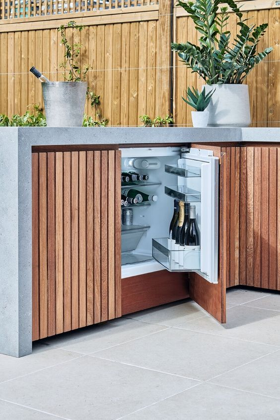 a small outdoor kitchen composed of two planked cabinets and with a concrete waterfall countertop, with potted herbs and a drink cooler