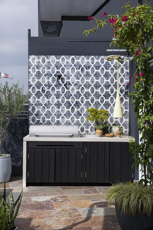 a small outdoor kitchen with a black cabinet and a cocnrete countertop, a grill, a pendant lamp and potted herbs is cool and fresh