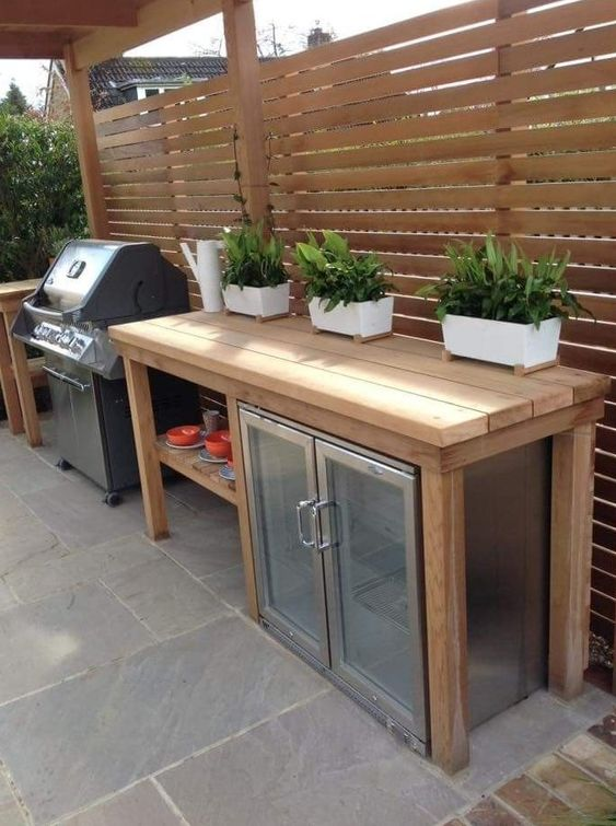 a small outdoor kitchen with a large wooden kitchen island and a drink cooler built-in under the top, a grill next to it is cool