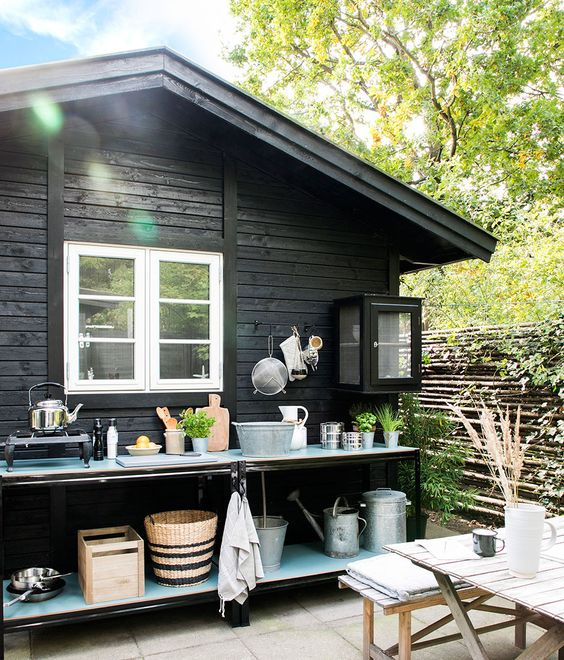 a small outdoor kitchen with open shelves, a small cooker and rustic buckets and baskets for storage, potted herbs