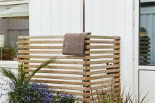 a small outdoor shower space with screens of planked wood, potted plants and blooms is a cool nook to refresh yourself