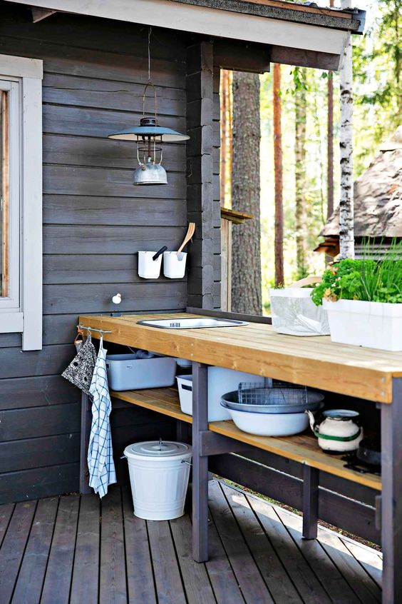 a small rustic Scandinavian outdoor kitchen with a planked floor, a long open shelving unit and pendant lamps is cool