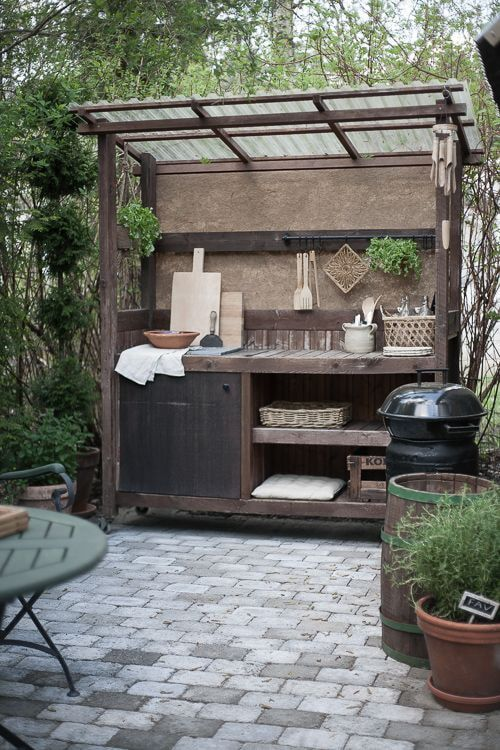 a small rustic outdoor kitchen of a single storage unit, with a roof, some shelves, a closed cabinet, potted greenery and cutting boards