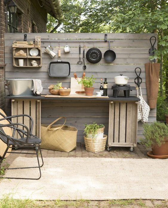 a small rustic outdoor kitchen with a planked wooden screen, a crate kitchen island, potted greenery and a black rattan chair