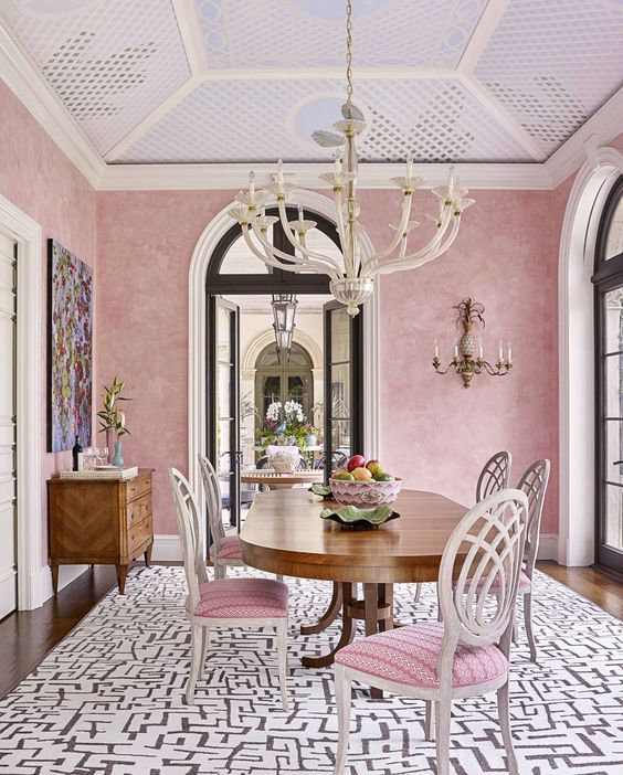 a sophisticated dining room with pink wallpaper walls, a decorated slanted ceiling, a vintage dining table and pink chairs plus a printed rug