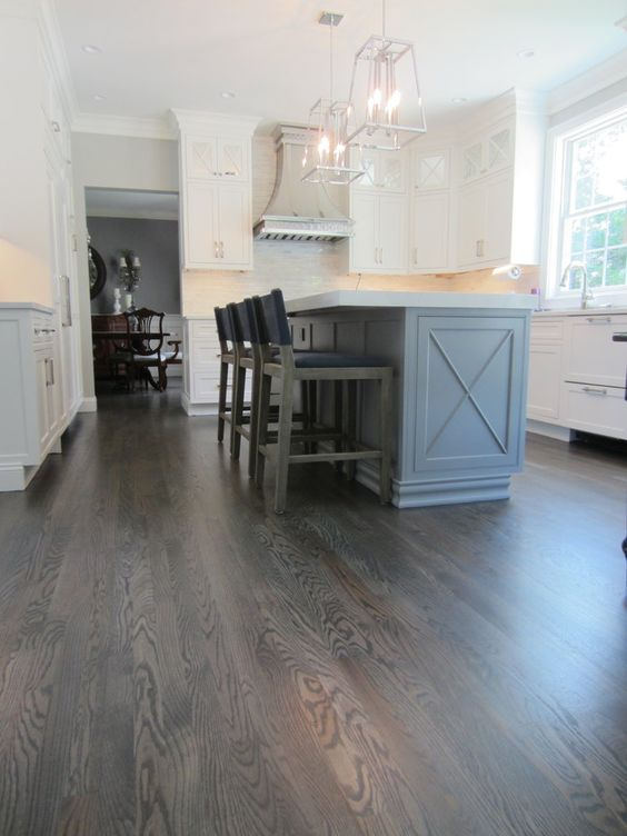 a sophisticated farmhouse kitchen with grey hardwood flooring, white cabinets and a light blue kitchen island, pendant lamps