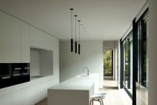 a sophisticated minimalist white kitchen with sleek cabinetry, built-in black appliances and black pendant lamps
