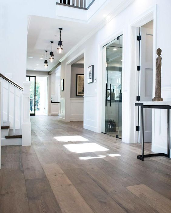 a sophisticated space with white paneled walls and hardwood floors that contrast, pendant lamps and lovely art here and there