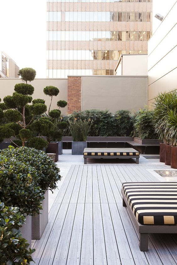 a stylish and elegant rooftop terrace with a neutral wooden deck, cool striped daybeds, lots of potted greenery and trees