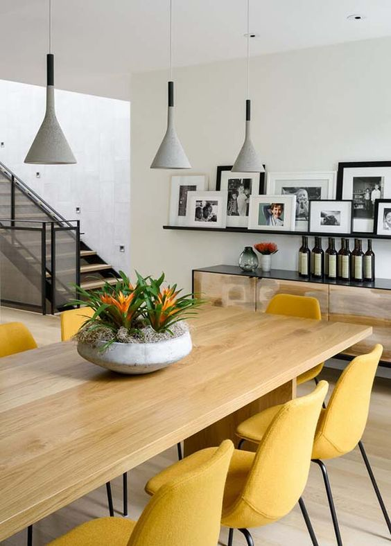 a stylish contemporary dining room with a large table, yellow chairs, grey pendant lamps, a dresser and a ledge gallery wall
