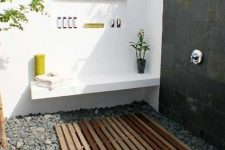 a stylish contemporary outdoor shower with pebbles and a wooden mate, a shelf and a niche to store various stuff