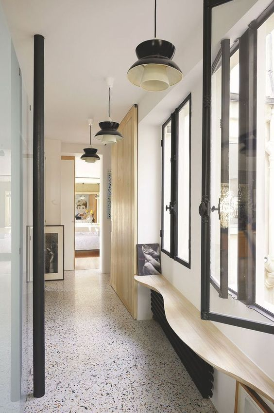 a stylish interior with white and light-stained wooden walls, a black and white terrazzo floor, windows and elegant retro lamps