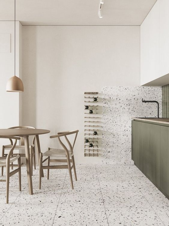 a stylish minimalist kitchen with green and white cabients, a terrazzo floor and a backsplash, black fixtures and a pendant lamp