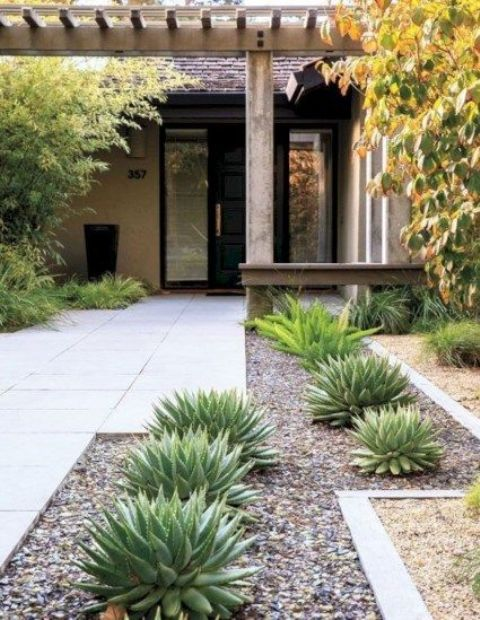 a stylish modern front yard with tiles covering it and succulents and trees is a chic space that welcomes inside