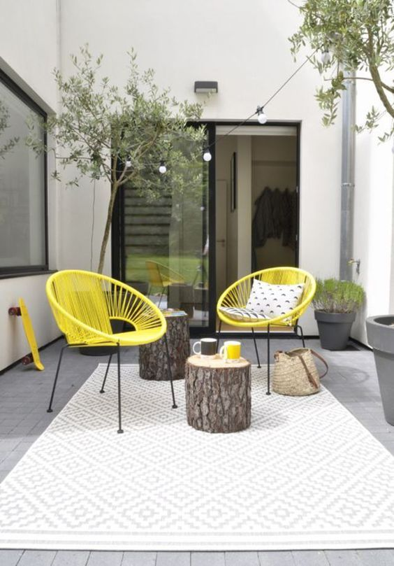 a stylish modern summer terrace with a printed rug, yellow chairs, tree stumps, potted greenery and a light string over the space
