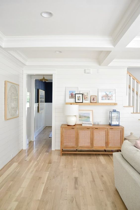 a stylish neutral living room with hardwood floors, elegant furniture, planked walls and a small gallery wall on a ledge