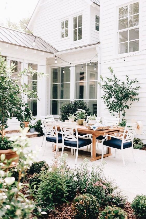 a stylish outdoor dining space with a sained table and white and navy chairs, potted plants and trees is a very cool space
