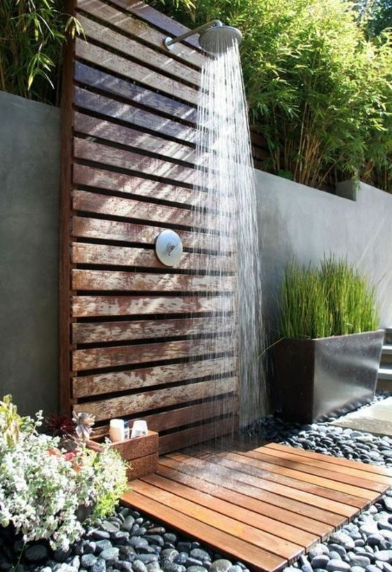 a stylish outdoor shower space with a concrete wall, a wooden planked wall and mate, a crate with stuff and growing plants