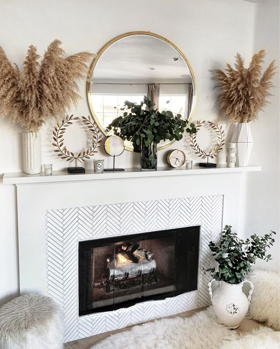 a summer boho mantel with pampas grass in vases, greenery arrangements, wreath decorations and clocks plus a round mirror