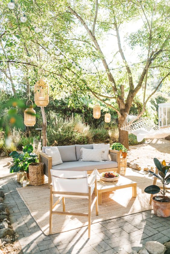 a summer boho patio with a grey sofa, neutral chairs, a low coffee table, lanterns hanging over the space, potted plants