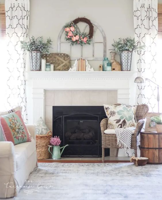 a summer farmhouse mantel with a faux flower wreath, greenery arrangements, books and candles, pillows and blankets around and some blooms