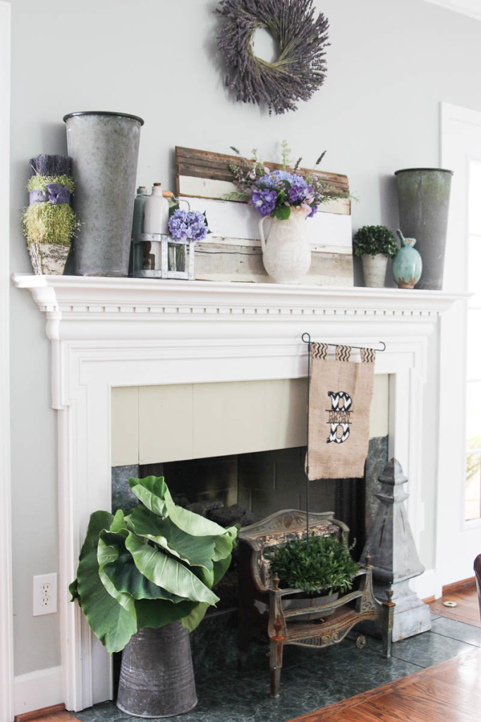 a summer farmhouse mantel with buckets, bright faux blooms and greenery, a lavender wreath, some milk bottles and oversized leaves