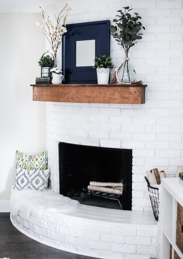 a summer farmhouse mantel with potted greenery, greenery blooming branch arrangements and a mirror in a wide frame