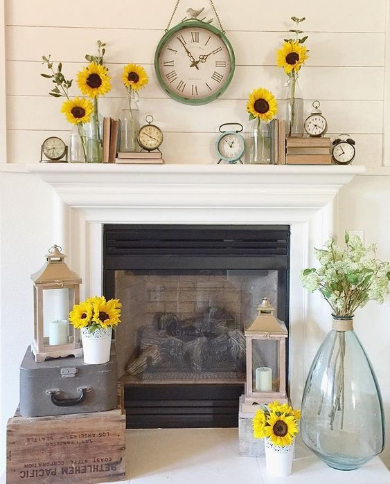 a summer mantel with stacked books, clocks, sunflowers in vases and jars and a large vintage clock and sunflowers for a sunny feel