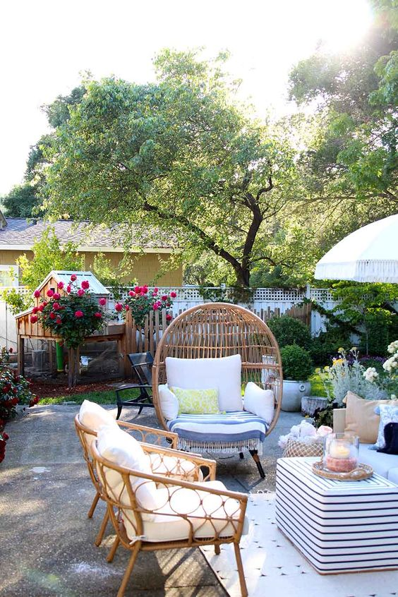 a summer outdoor space with rattan furniture, a striped coffee table, printed textiles and greenery and blooms is welcoming