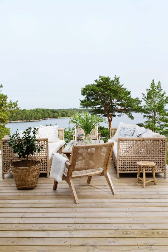 a summer terrace with a river view, wooden and rattan furniture, trees and greenery around and printed textiles