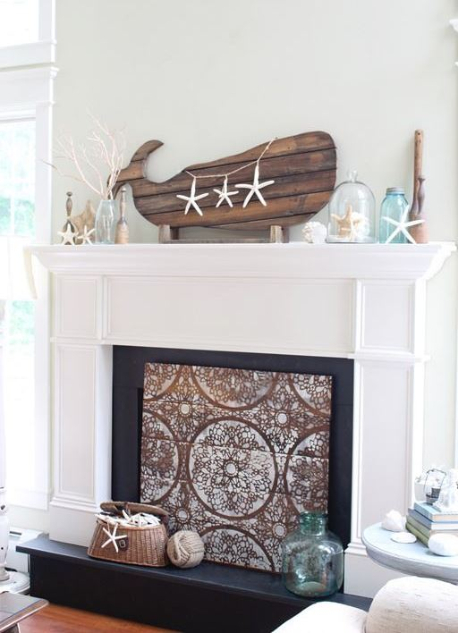 a super cool coastal mantel with starfish, a cloche with one of them, jars and vases, branches and a planked whale