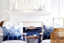 a super cool seaside mantel with fabulous white artwork with pressed sea creatures, vases and wooden fish