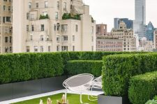 a super elegant and refined contemporary rooftop terrace with greenery walls, a small lawn and a couple of chairs is very inviting