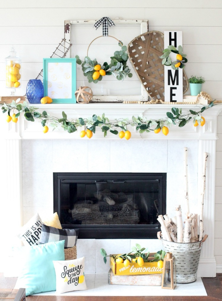 a super fun summer mantel with a greenery and lemon garland, lemons on the wreaths and in a jar, frames and potted plants
